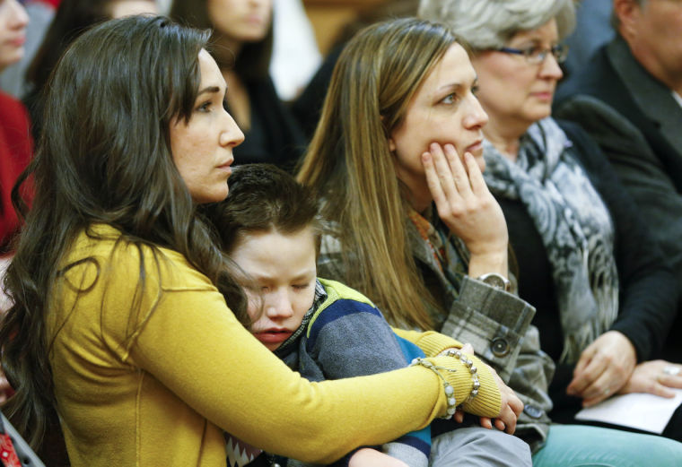 Kiley Klug, left, holds her seven-year-old son Owen while listening to testimony Tuesday afternoon to the House Standing Committee on Health and Human Services on HB 2011, a bill that would allow for cannabis to be used for medical purposes. (CHRIS NEAL/THE CAPITAL-JOURNAL)